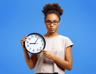 Serious student shows clock, demonstrates its time to work! Photo of african american girl wears casual outfit on blue background. Emotions and pleasant feelings concept.