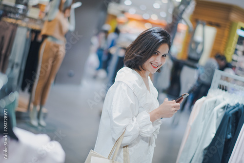 af5f4e0e87e Young Asian beautiful woman shot hair shopping new clothes in a shopping  mall store. Woman standing and holding a shopping bag and phone which  looking to ...