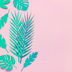 Wall Mural - Turquoise green tropical leaves on pink background , flat lay. Copy space. Paper tropical leaves