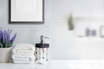 Mockup bath towel with liquid soap bottle and houseplant on white table in white room.