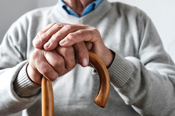 Hands of an elderly man resting on a walking cane