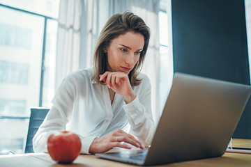 Young entrepreneur female using mobile laptop for looking a new business solution during work process at office.Blurred background