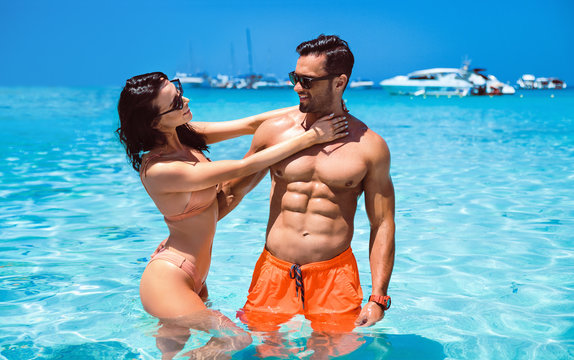 Portrait of a sensual young couple posing in a clear, tropical water