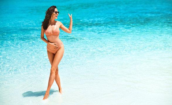 Sensual young woman posing on a beautiful tropical beach