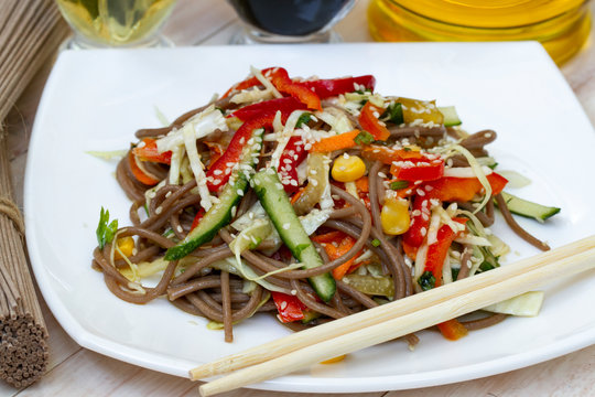 Japanese soba salad with vegetables and sesame close-up on a plate on the table. vegetarian Asian food. noodles salad. buckwheat noodle with vegetables.