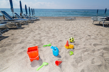 children's toys on the beach sand against turquoise sea.