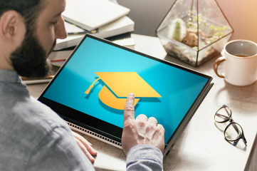 Bearded man with laptop at his desk. He presses on the graduation hat icon. Concept of modern technology in education. Image