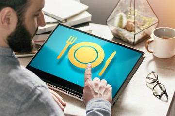 Bearded man with laptop at his desk. He presses on the restaurant icon. Concept of food order via internet. Image