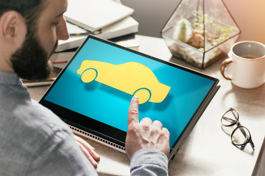 Bearded man with laptop at his desk. He presses on the car icon. Concept of car rent, buying, insurance in web. Image