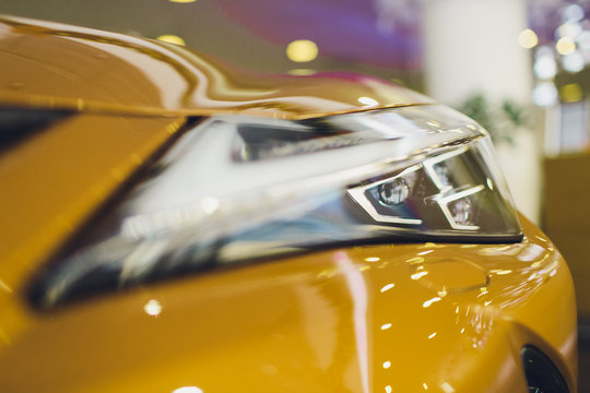 Car detailing series: Clean headlights of yellow sports car.