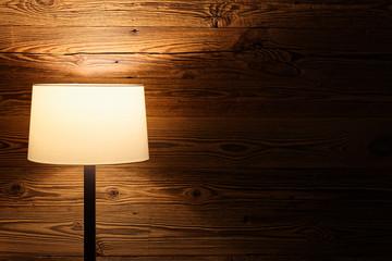 Indoor scene of a floor lamp against wooden wall