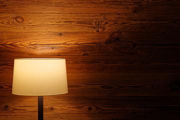 Indoor lighting by floor lamp at wooden wall