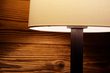 Light of a floor lamp on a wooden wall