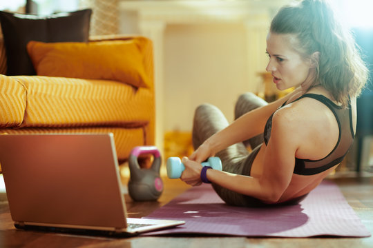 woman using online fitness site in laptop and doing exercises