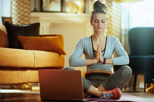 woman meditating using online yoga training program in laptop