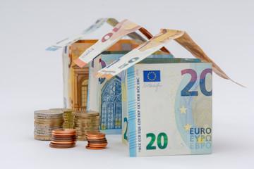 Fototapeta Trois maisons faites en billets de 10, 20, et 50 euros, avec quelques pièces de monnaie obraz