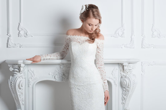 beautiful bride in a wedding dress standing in a chic hotel room