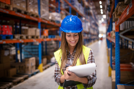 Female warehouse worker checking supply in large distribution warehouse storage area. Smiling confident woman holding checklist.