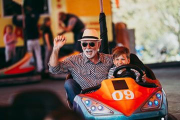 Foto op Plexiglas Amusementspark Grandfather and grandson having fun and spending good quality time together in amusement park. They enjoying and smiling while driving bumper car together.