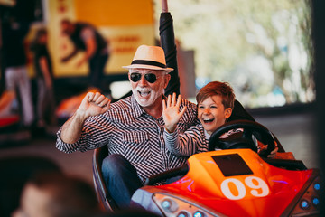 Printed roller blinds Amusement Park Grandfather and grandson having fun and spending good quality time together in amusement park. They enjoying and smiling while driving bumper car together.