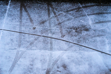 car tyre traces on parking spot in winter - top down