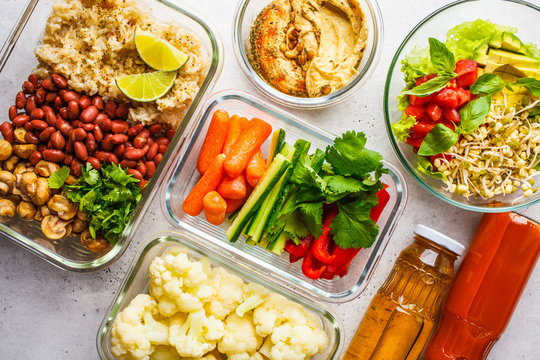 Healthy vegan food in glass containers, top view. Rice, beans, vegetables, hummus and juice.