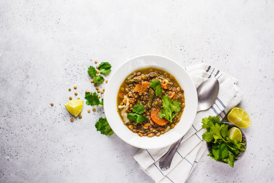 Lentil soup with vegetables in a white plate, white background, top view. Plant based food, clean eating.