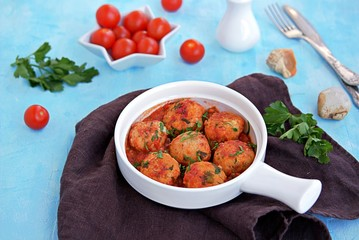 Fish meatballs in tomato sauce in a white ceramic pan on a light blue concrete background.