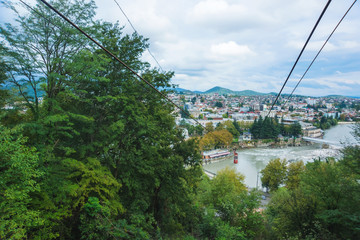Old cable car in Tbilisi. Red cab on the cable car over Turtle lake. Green trees and buildings. Rest in Georgia. Funicular over the city. Wall mural