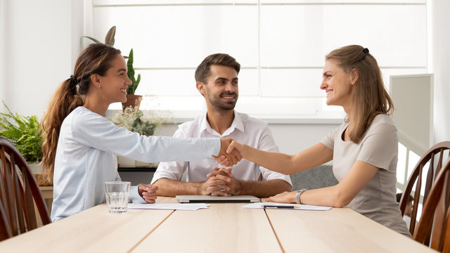 Happy female business partners handshake sign contracts with lawyer mediation
