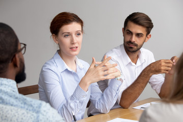 Confident female leader speak at group training explain corporate strategy