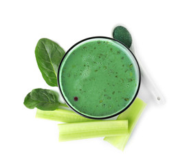 Glass of spirulina smoothie, powder, spinach and celery on white background, top view