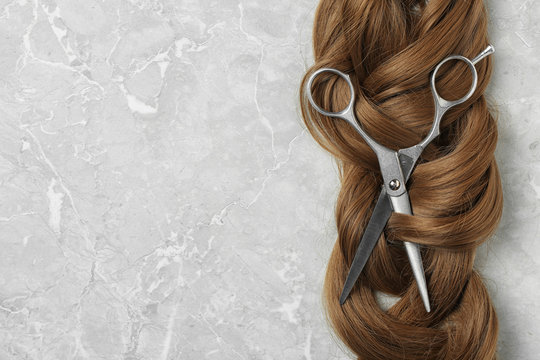 Flat lay composition with brown hair, scissors and space for text on grey background. Hairdresser service