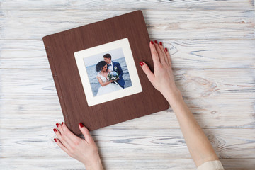 brown photo book with  leather cover.  stylish wedding photo album. a person opens a photobook. Family photoalbum on the table. the womans hand holding a family photo album Wall mural