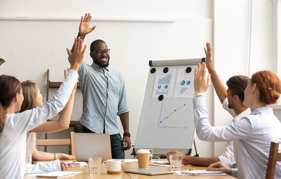 Business team voting concept, african coach and employees raise hands