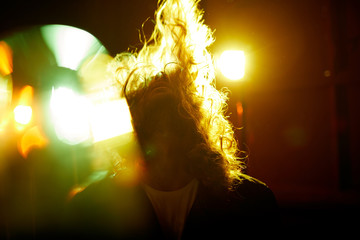 Energetic young male rock musician shaking hair while performing in disco lights at musical concert