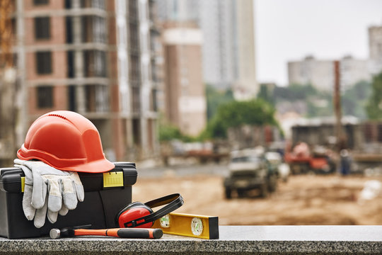 Set of safety workwear, toolbox and other professional equipment lying on stone surface against construction site. Building concept