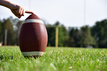 Close-up photo of a football on a sunny day being held with a goal post, football field and trees in the background