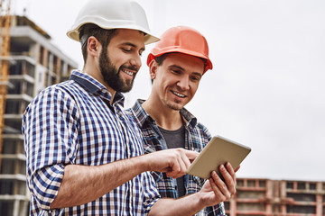 Fototapeta Working in team. Two young and cheerful builders in protective helmets are using digital tablet and working while standing at construction site obraz