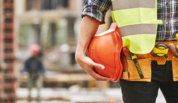 Construction worker. Cropped photo of male professional builder in working uniform with construction tools holding a safety red helmet while standing outdoor of construction site