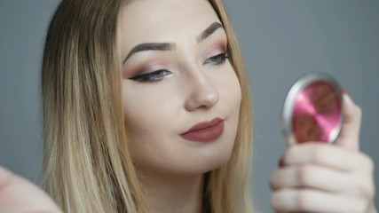 Wall Mural - beautiful girl doing makeup in front of the mirror, young woman paints eyelashes with mascara and looks in the mirror on studio background, the concept of cosmetics and beauty