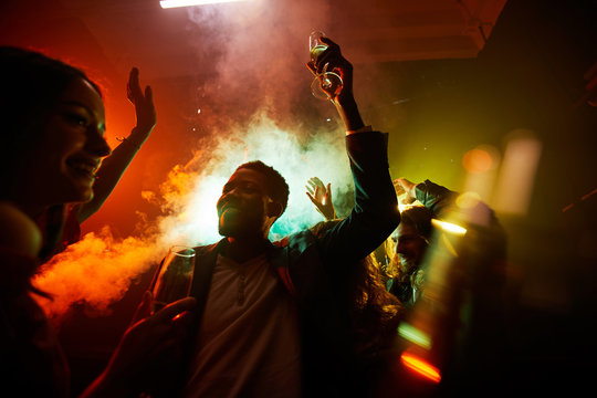Crowd of cheerful hilarious young multiethnic people drinking alcohol and dancing in smoke at noisy party