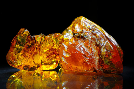 Amber. Beautiful colored pieces of amber. Amber texture. Red-yellow amber with bubbles, waves, divorces and color transitions. Natural mineral Sunstone. Material for jewelers. Crystal