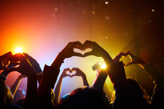 Crowd of unrecognizable fans joining hands in shape of hearts while expressing love in relation to performer at concert