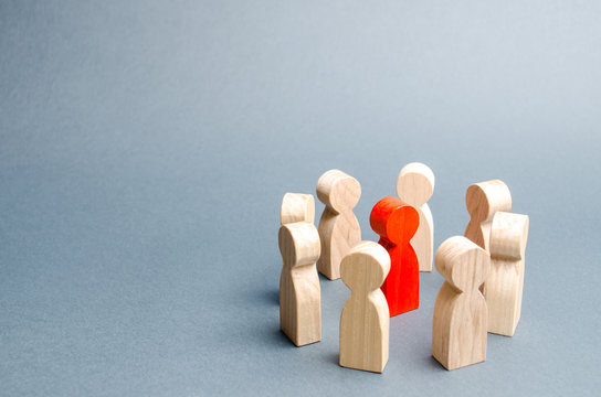 A circle of people surrounds a red person. Communication. Business team, teamwork, team spirit. Wooden figures of people. A circle of people. discussion, cooperation, cooperation. Selective focus