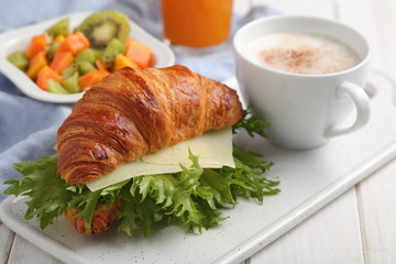 French breakfast: croissant sandwich with cheese, fruit salad, and coffee