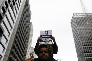 A boy holds a sign with the image of late former South African President Nelson Mandela during a demonstration against military operation that killed Evaldo Rosa dos Santos with 80 shots into his car in Rio de Janeiro, in Sao Paulo