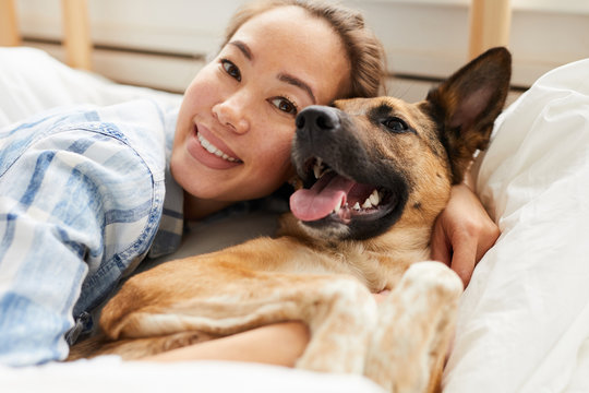 Portrait of smiling Asian woman hugging dog lying on bed  together and looking at camera, copy space