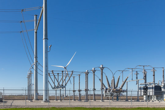 electrical substation with a wind turbine in background supplying the power
