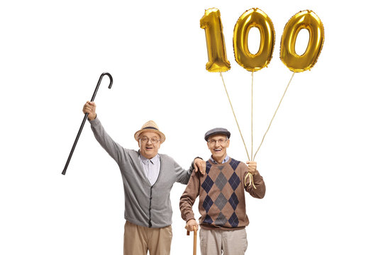 Happy senior men with a golden number hundred balloon